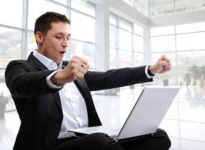 successful man with laptop in modern white office with glass around